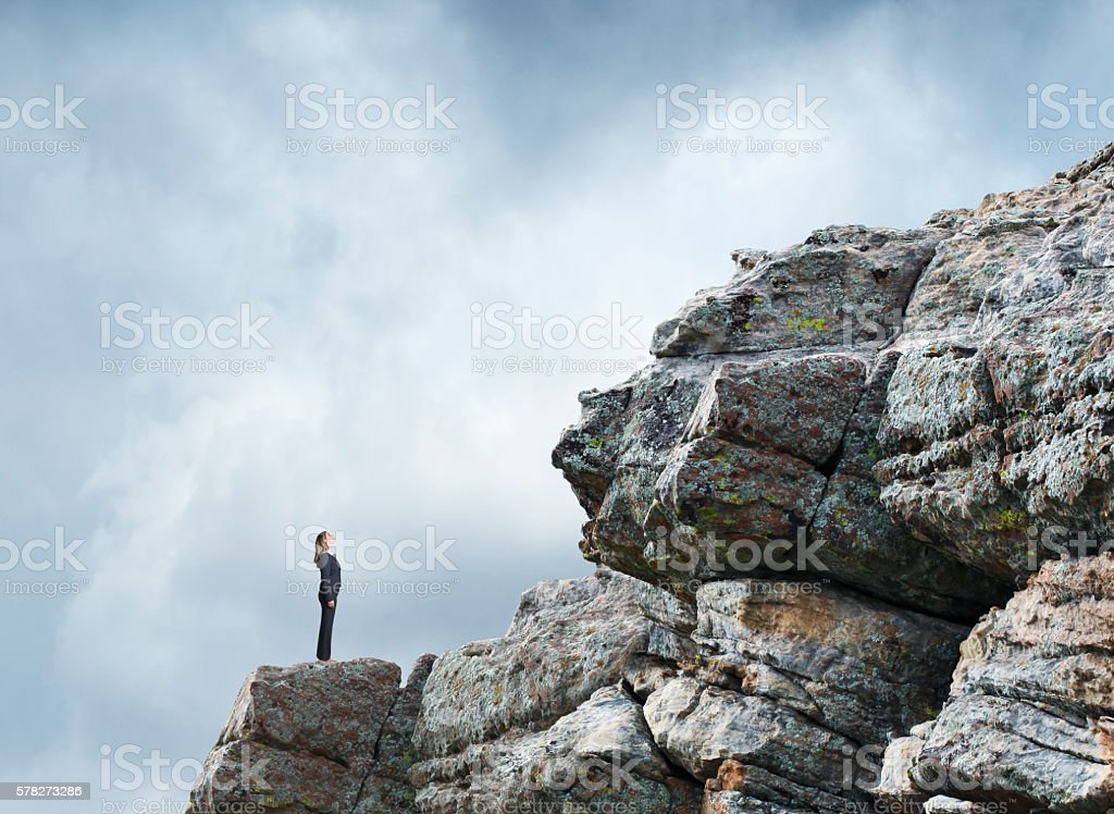 Businesswoman On A Rocky Slope Looks At The Challenges Ahead stock photo