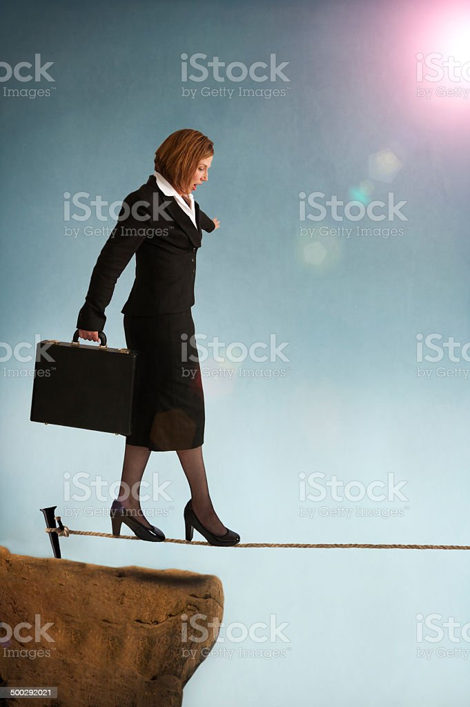 businesswoman on a tightrope stock photo