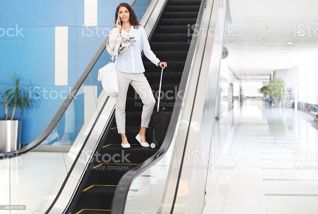 Businesswoman on escalators at airport stock photo