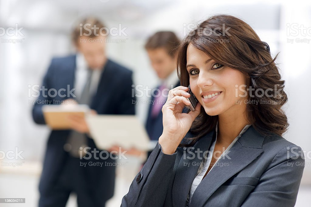 A businesswoman on her cell phone with two businessmen royalty-free stock photo