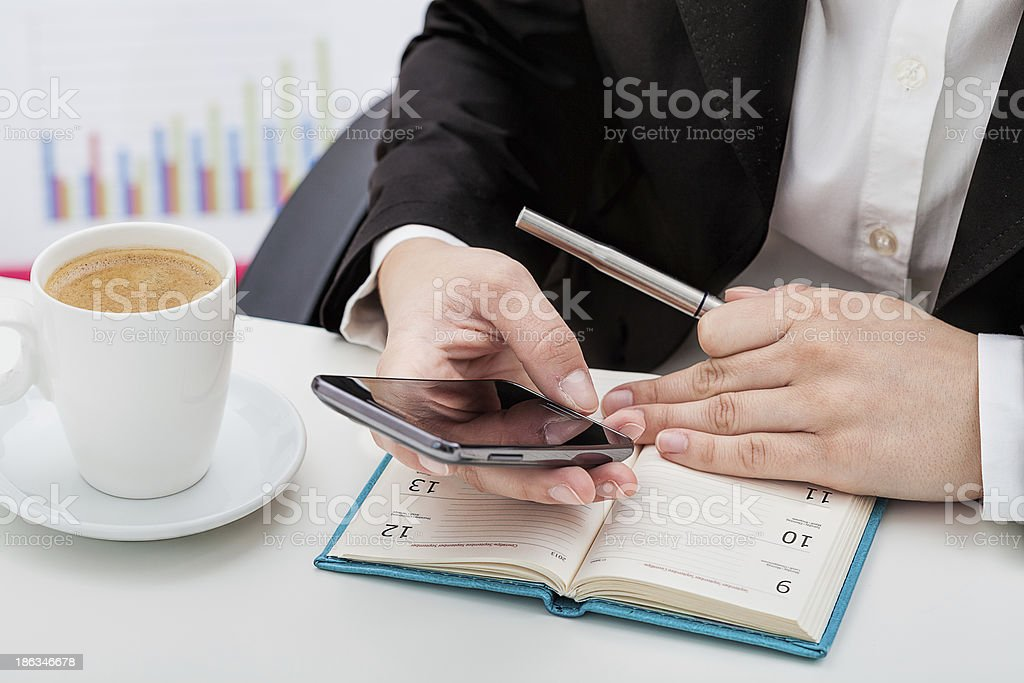 Businesswoman on her smartphone with a day planner and pen stock photo