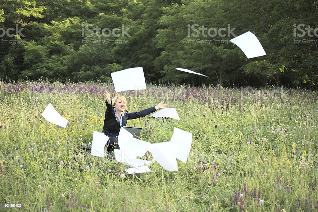 Businesswoman on nature with laptop catch documents royalty-free stock photo