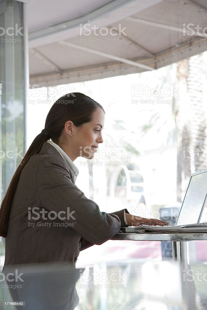 Businesswoman on outdoor patio with laptop royalty-free stock photo