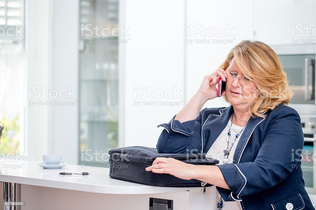 Businesswoman on Phone ready to go out stock photo