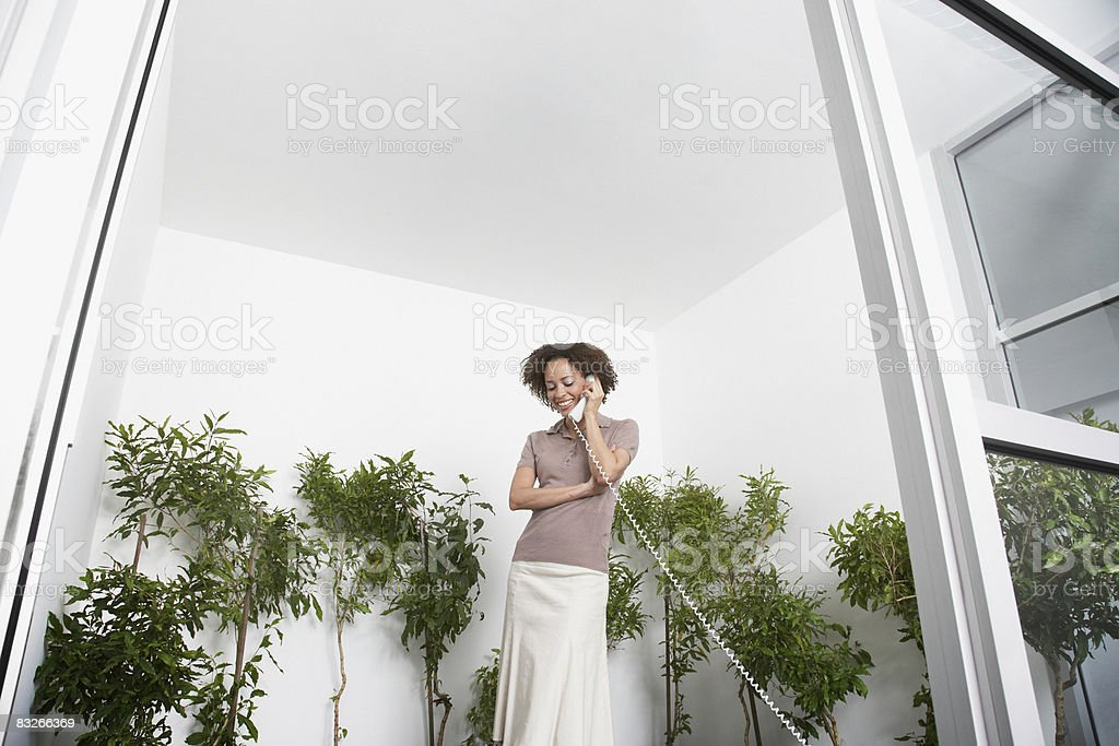 Businesswoman on phone surrounded by trees stock photo