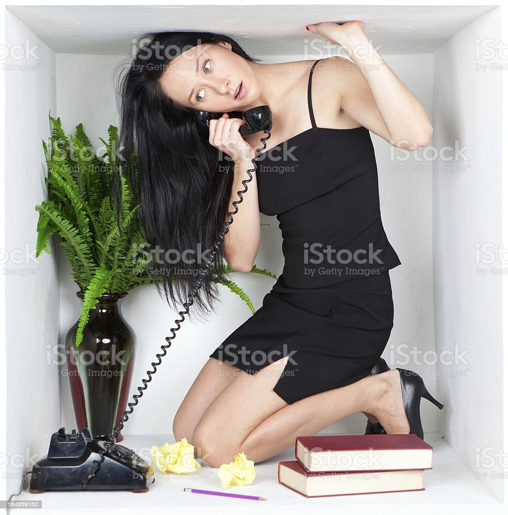 Businesswoman on phone trapped inside small cubicle stock photo