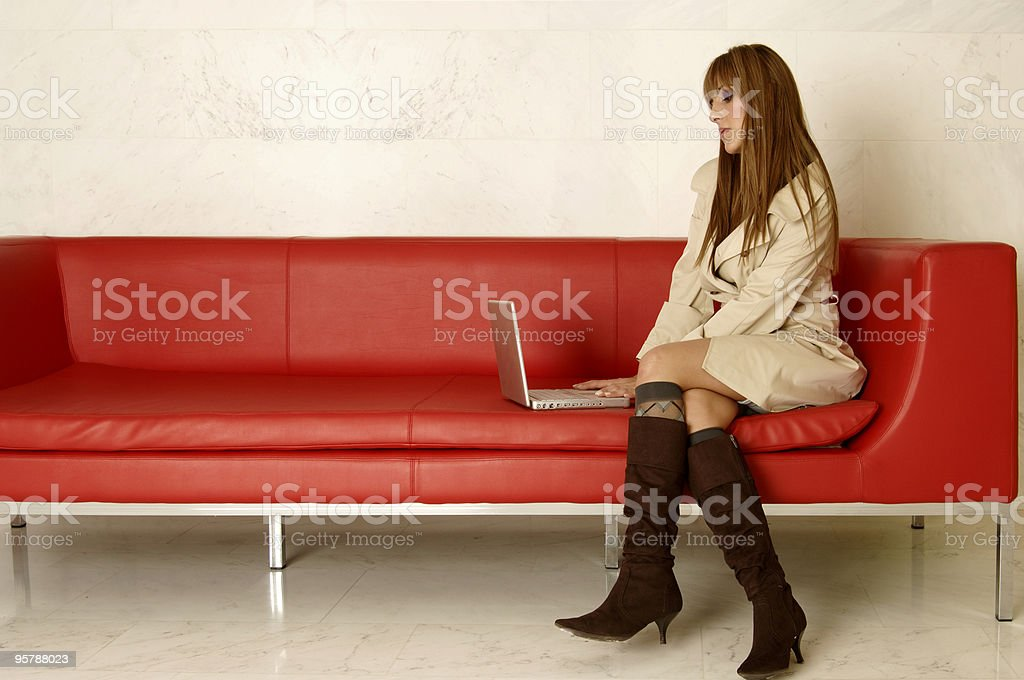 Businesswoman on red sofa using laptop computer royalty-free stock photo
