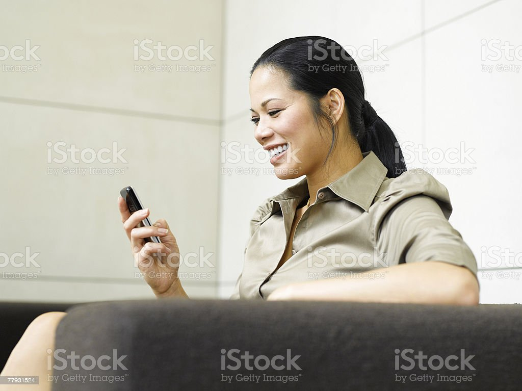 Businesswoman on sofa with mobile phone royalty-free stock photo
