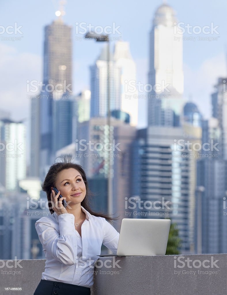 businesswoman on the phone and using laptop in Dubai stock photo