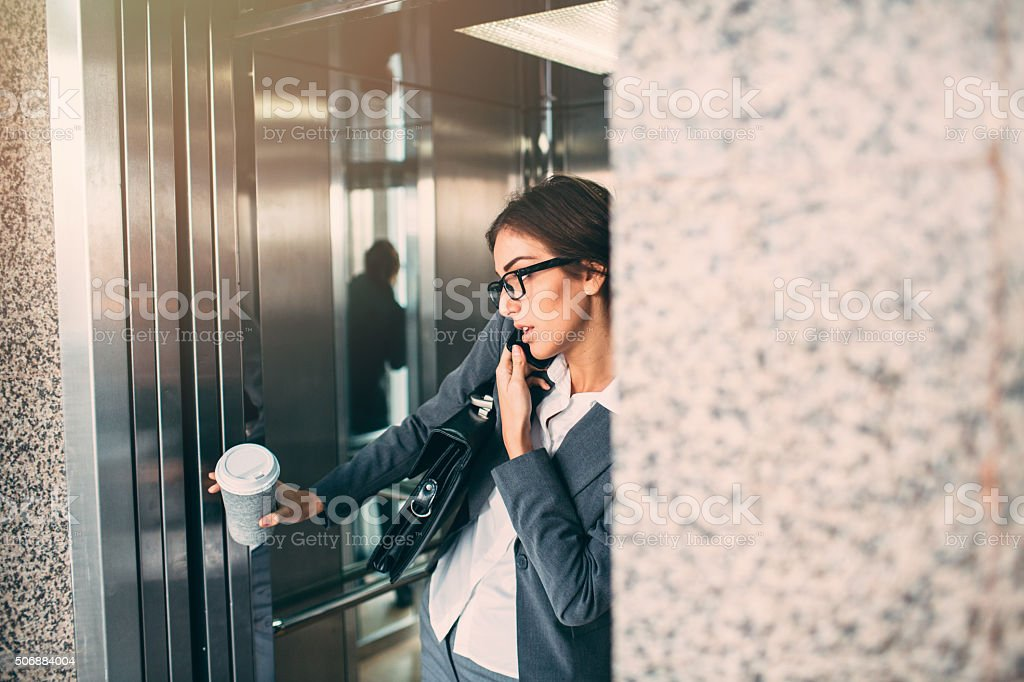 Businesswoman On The Phone In The Elevator stock photo