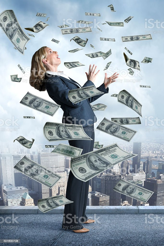 Businesswoman On Top Of Building With Money Raining Down stock photo