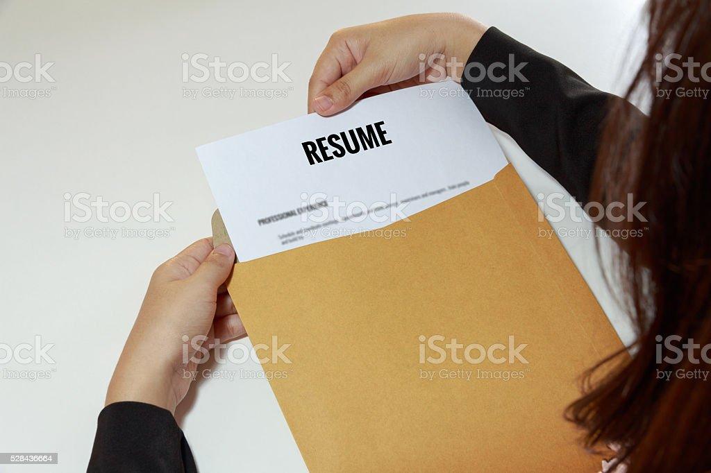 Businesswoman opening resume in letter envelope stock photo