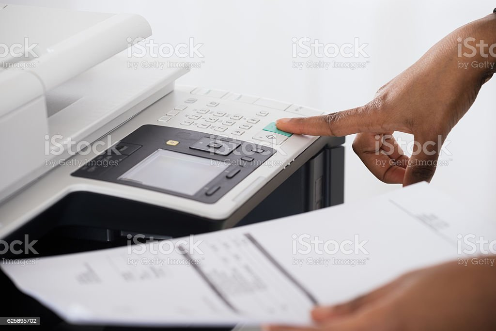 Businesswoman Operating Printer In Office stock photo