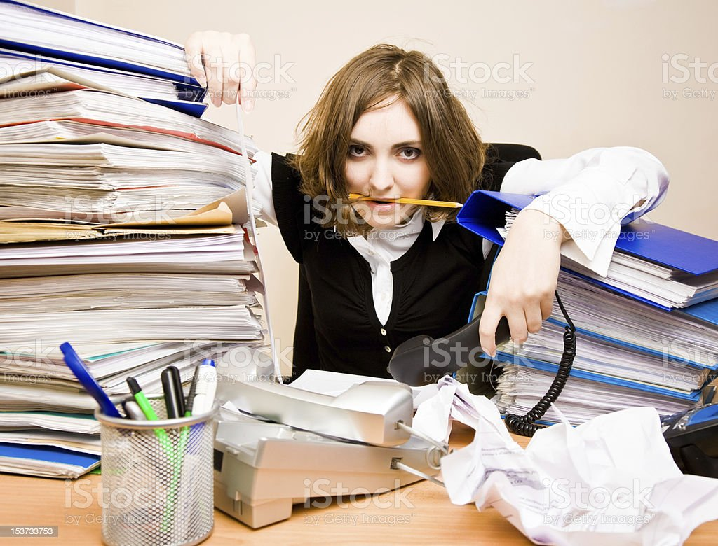 Businesswoman overwhelmed by phones and stacks of paperwork royalty-free stock photo