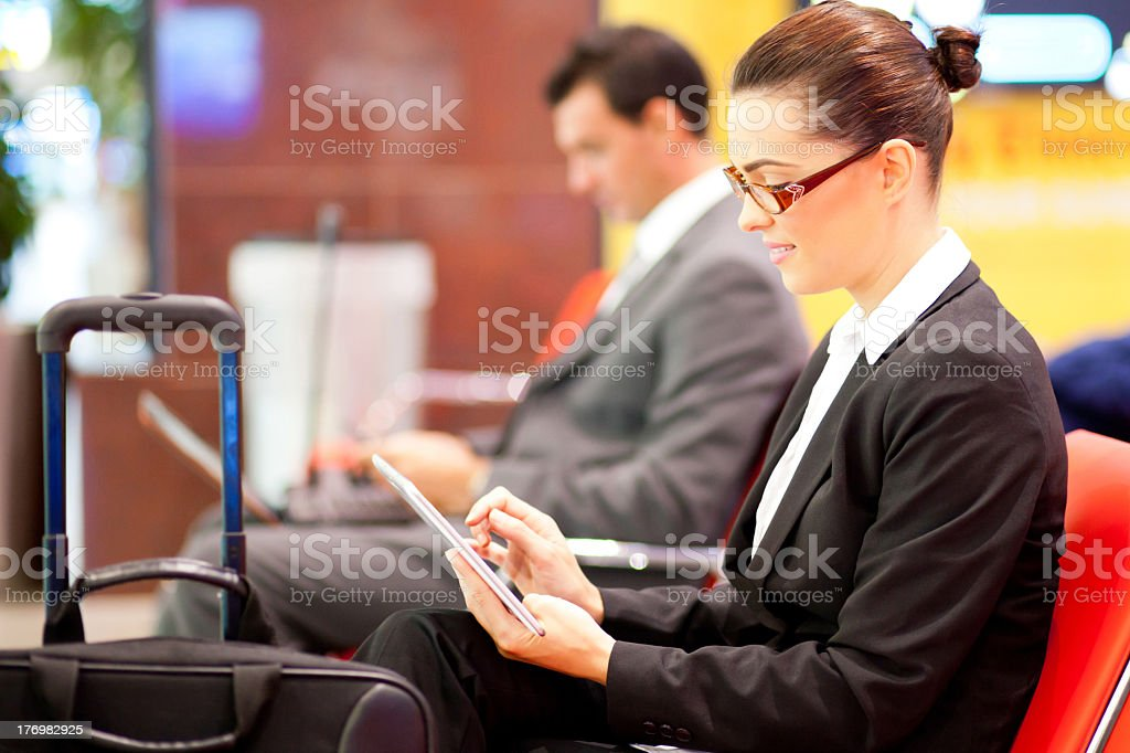Businesswoman passing time at the airport using her tablet royalty-free stock photo