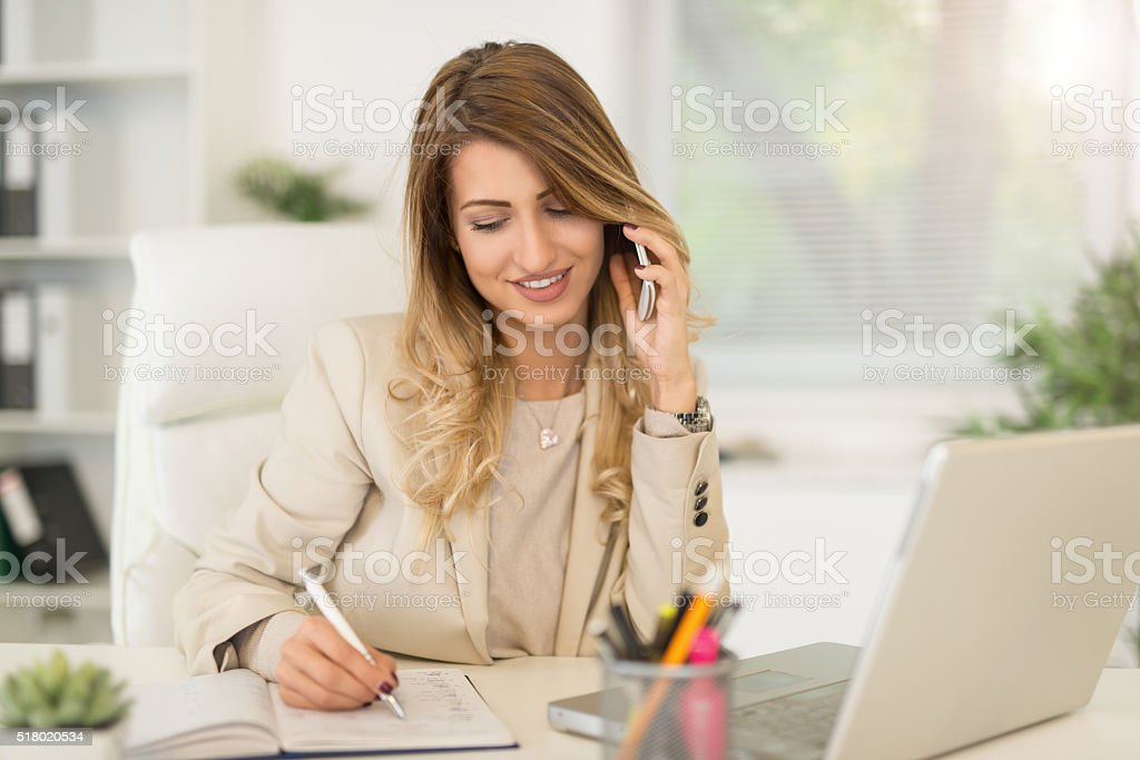 Businesswoman Phoning In Office stock photo
