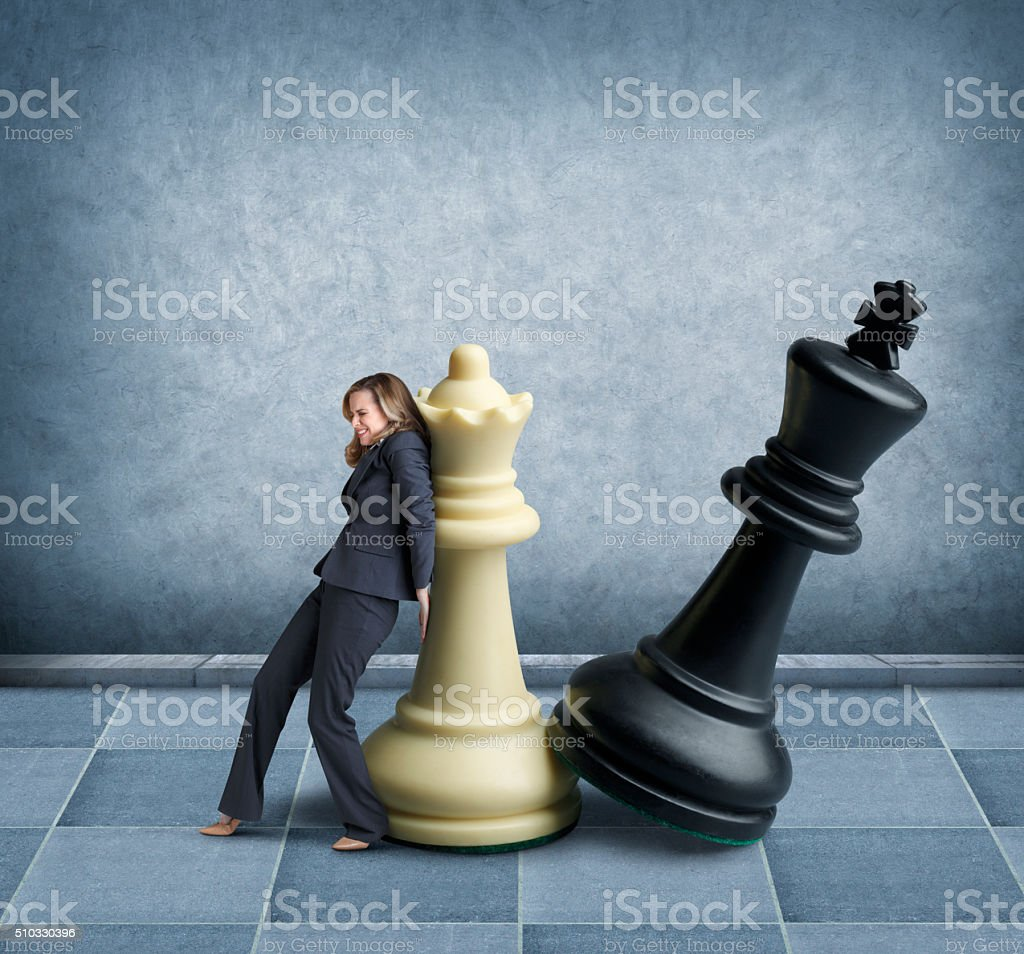 Businesswoman playing chess with oversized chess pieces stock photo