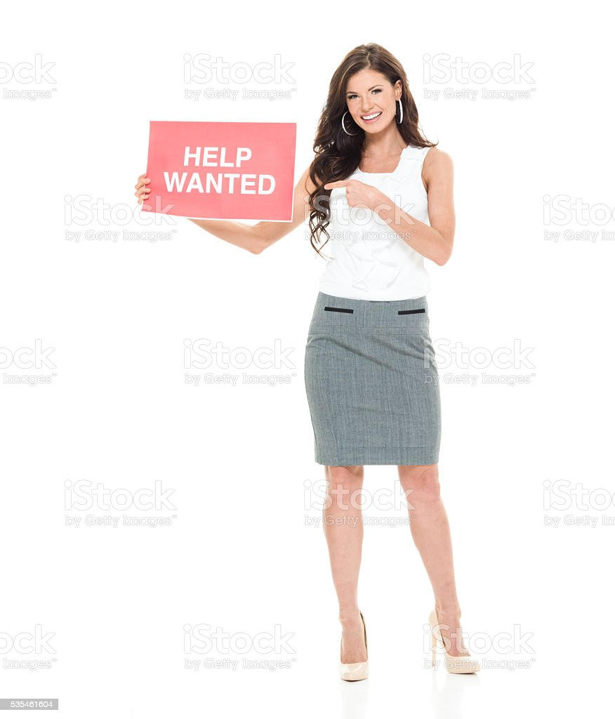 Businesswoman pointing at help wanted sign stock photo