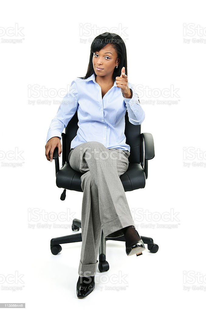 Businesswoman pointing sitting on office chair stock photo