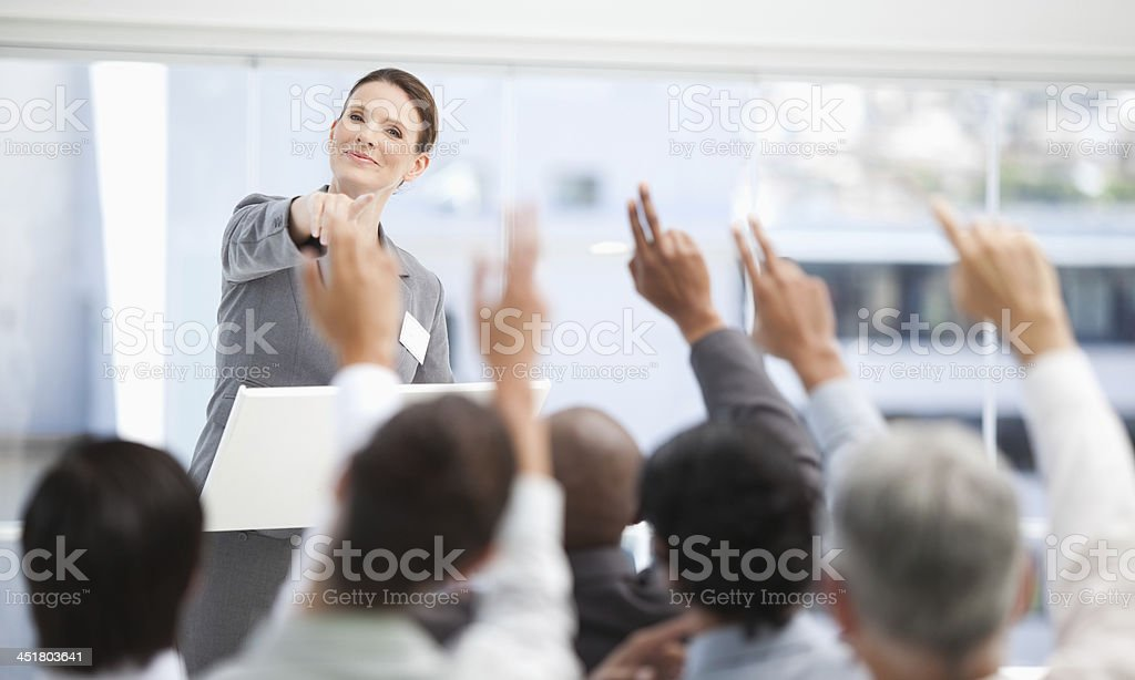 Businesswoman pointing towards a business team who have their ar royalty-free stock photo