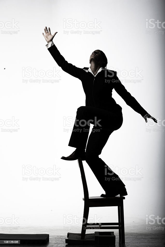 Businesswoman Posing and Standing on Chair, Low Key stock photo