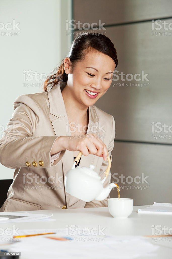 Businesswoman pouring tea stock photo