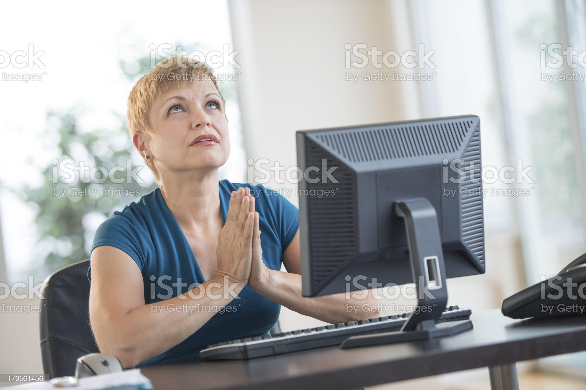 Businesswoman Praying While Sitting At Desk royalty-free stock photo