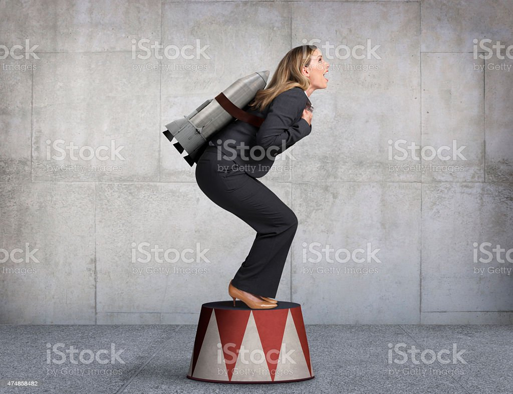 Businesswoman Preparing For Takeoff On Circus Pedestal stock photo