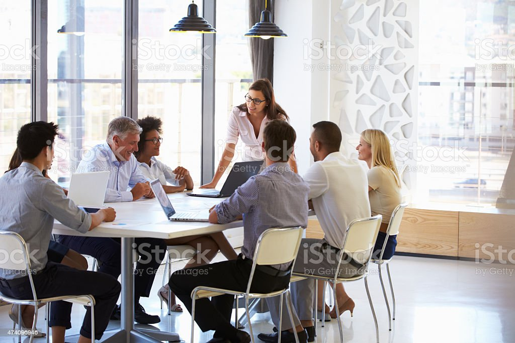 Businesswoman presenting to colleagues at a meeting stock photo
