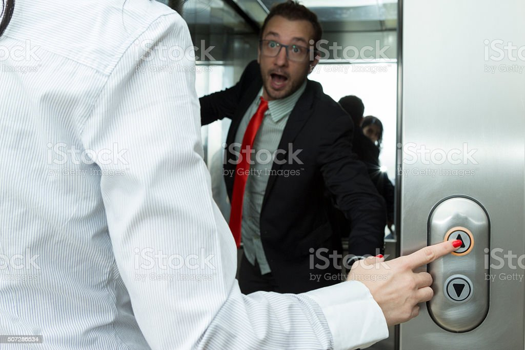 Businesswoman pressing elevator up button and confused Businessman stock photo