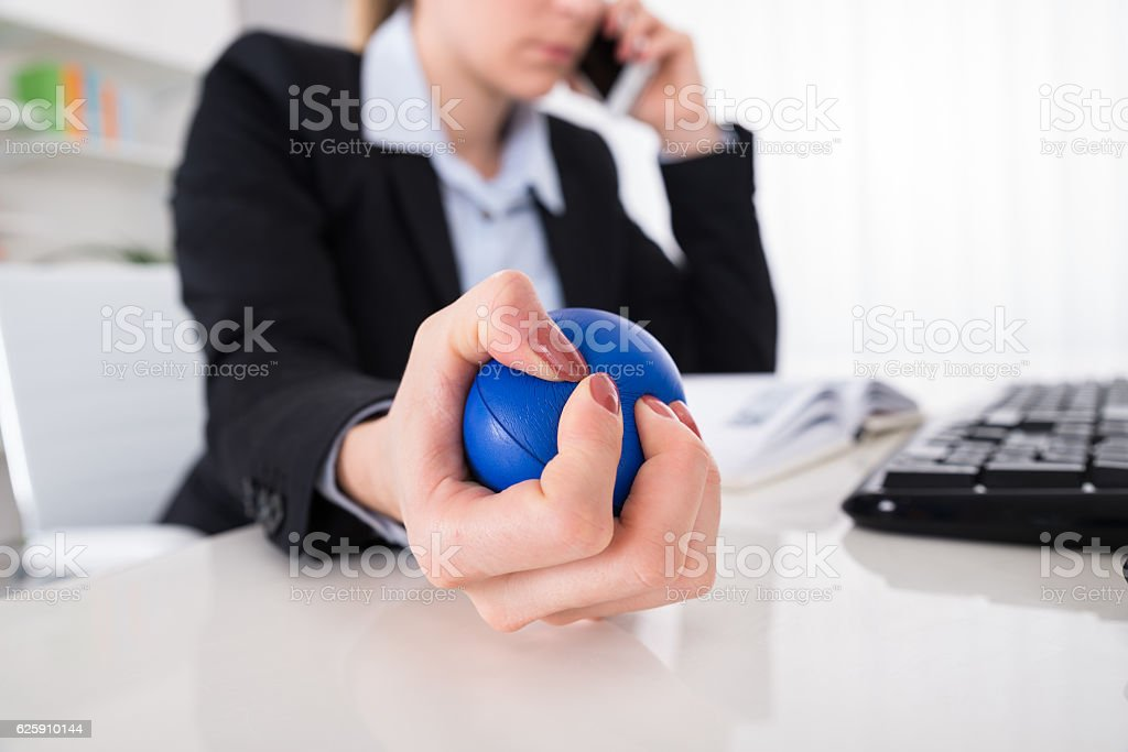 Businesswoman Pressing Stressball At Desk stock photo