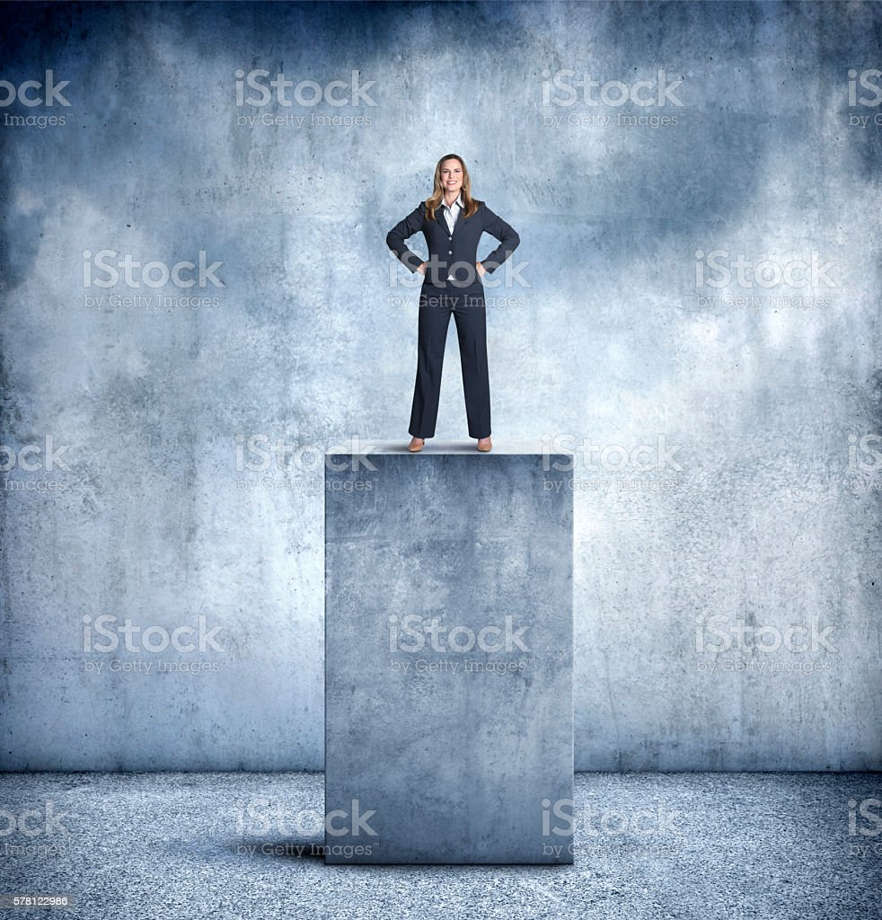 Businesswoman Proudly Standing On Top Of Large Concrete Pedestal stock photo