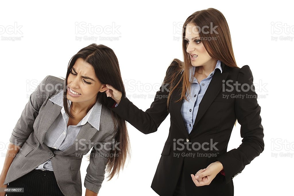 Businesswoman pulling colleague's ear stock photo