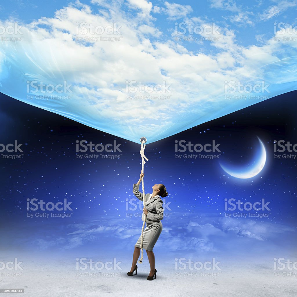 Businesswoman pulling down the sky stock photo