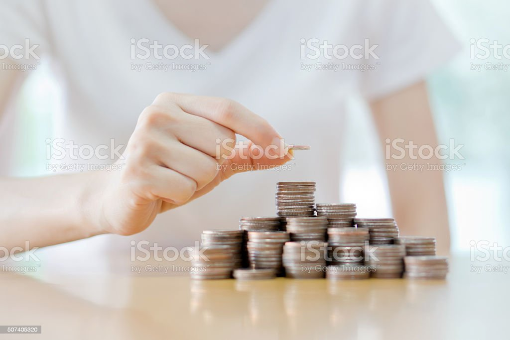 Businesswoman Putting Coin To Rising Stack Of Coins stock photo