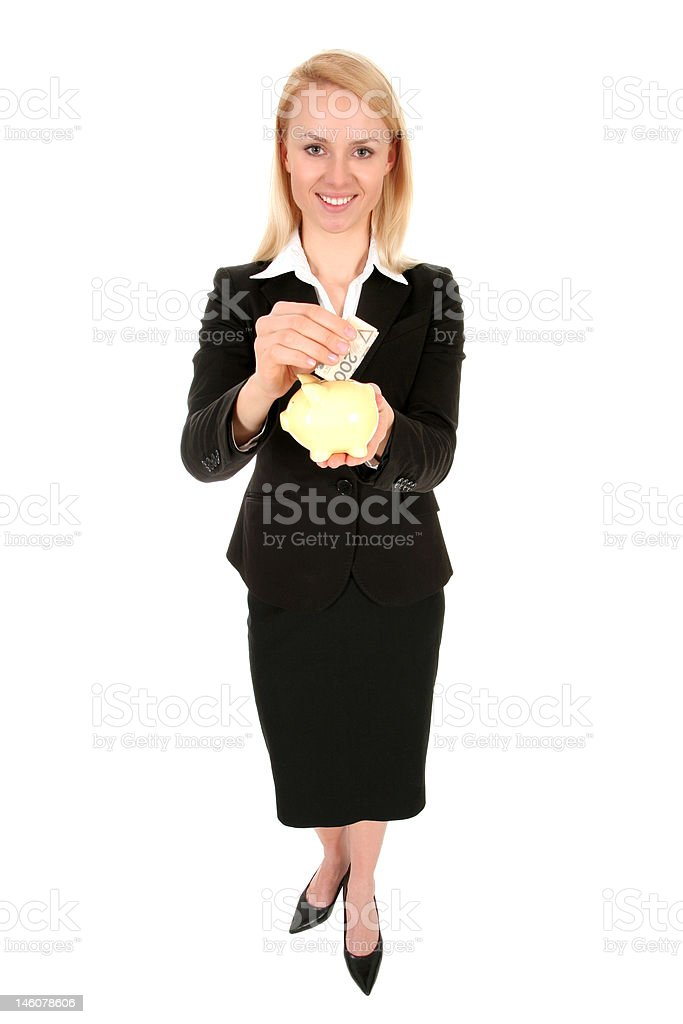 Businesswoman putting money in piggy bank royalty-free stock photo