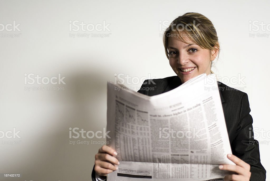 Businesswoman reading a newspaper against white background stock photo