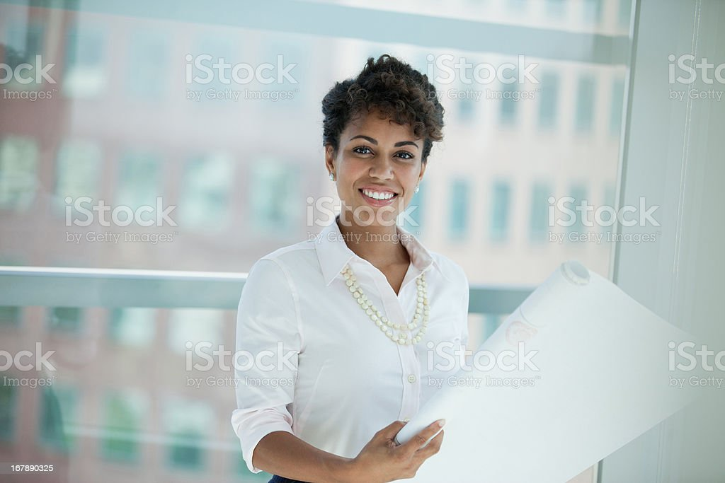 Businesswoman reading blueprints in office royalty-free stock photo