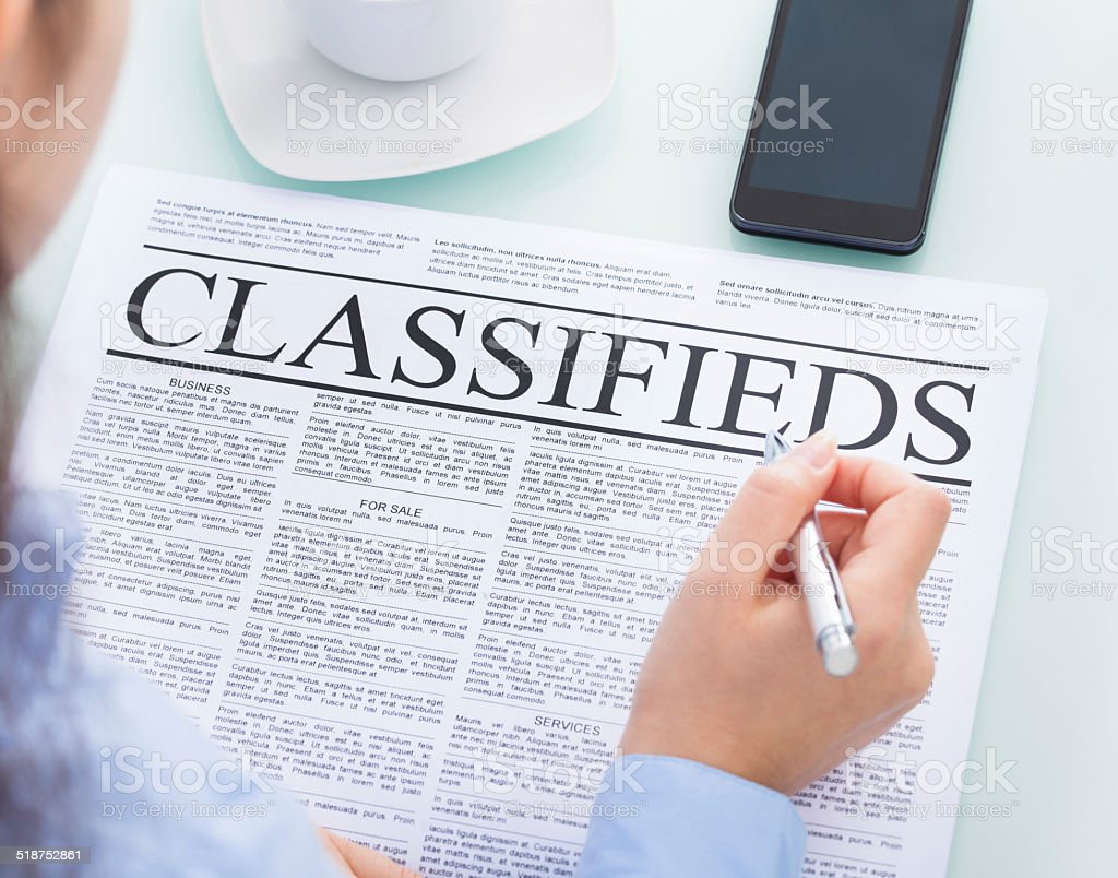 Businesswoman Reading Classifieds stock photo