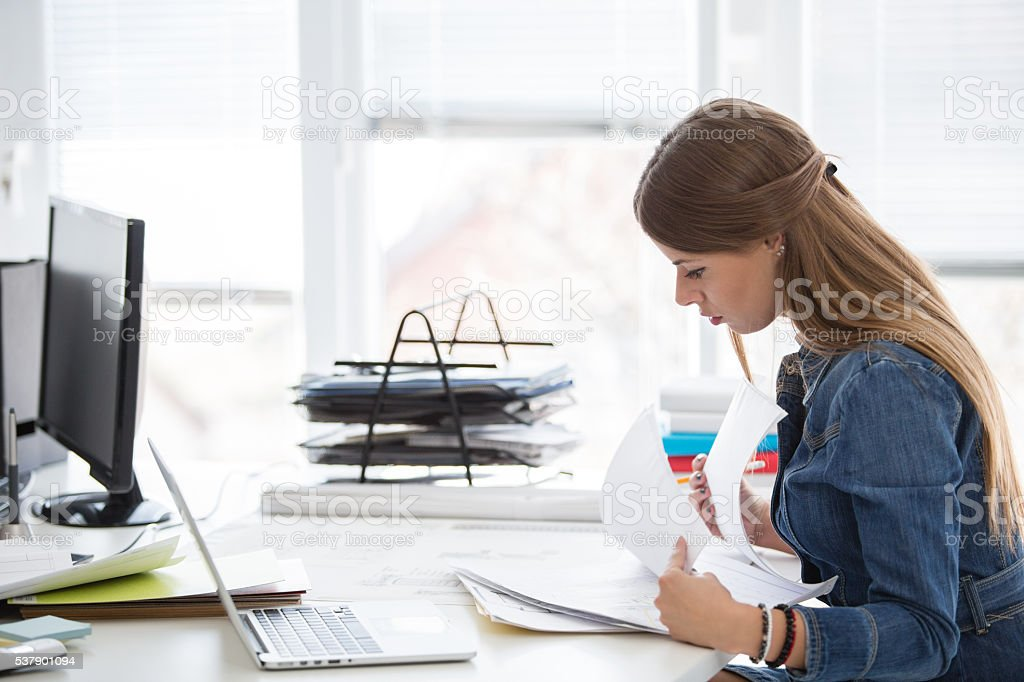 Businesswoman reading documents at desk in office stock photo