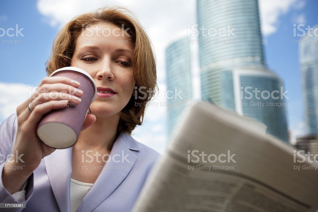Businesswoman reading newspaper and drinking coffee on the go stock photo