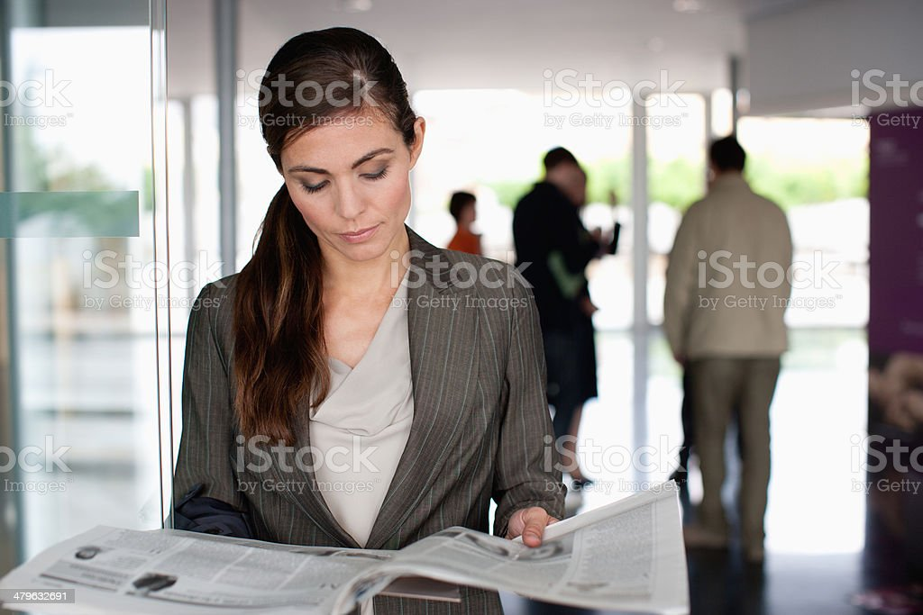 Businesswoman reading newspaper in office lobby stock photo