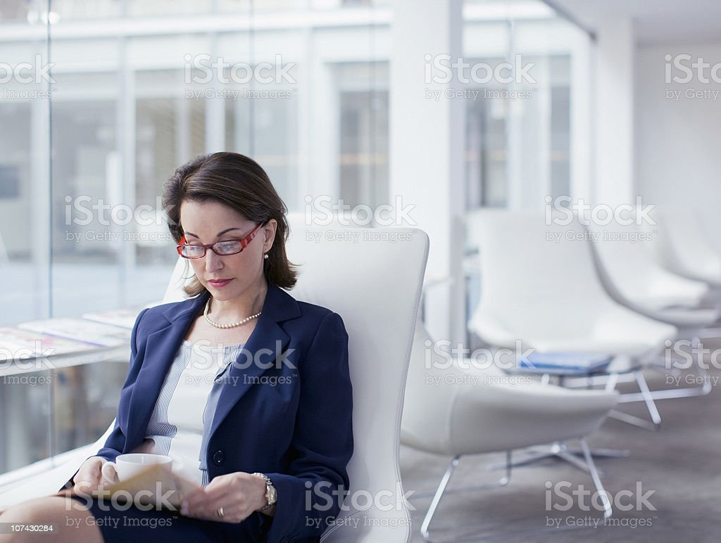 Businesswoman reading newspaper in waiting area royalty-free stock photo