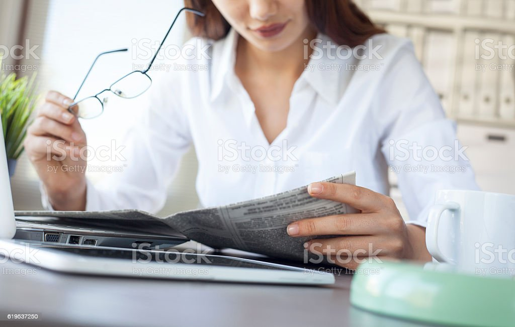 Businesswoman reading newspaper on worktable stock photo