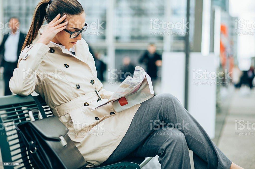 Businesswoman reading newspaper stock photo