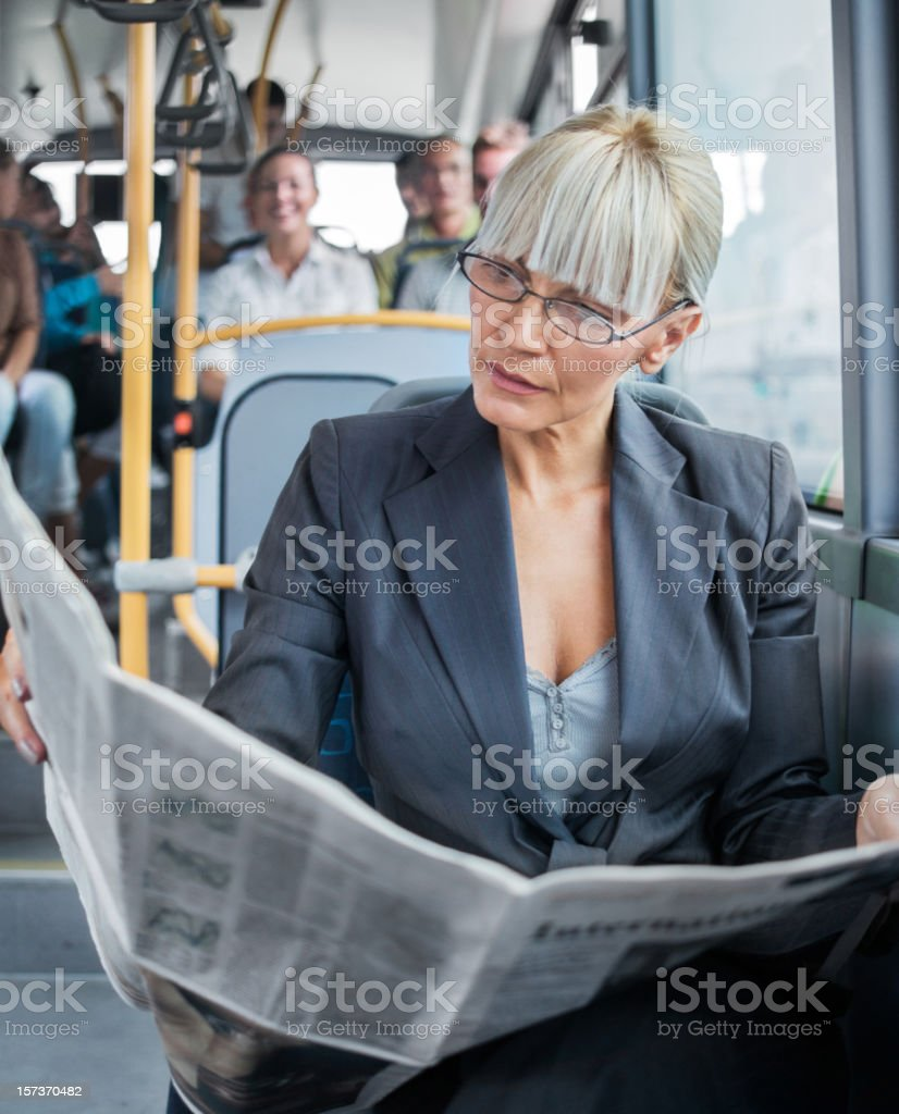 Businesswoman reading newspapers in bus. royalty-free stock photo