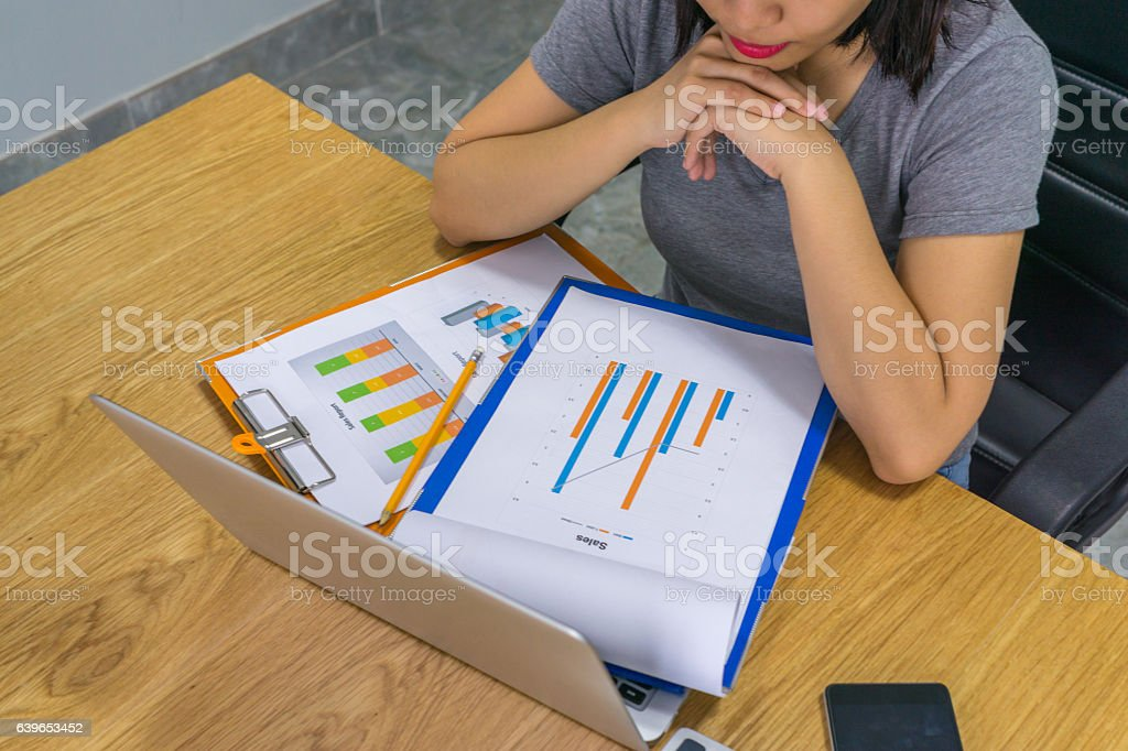 Businesswoman reading reports with laptop and smartphone beside stock photo