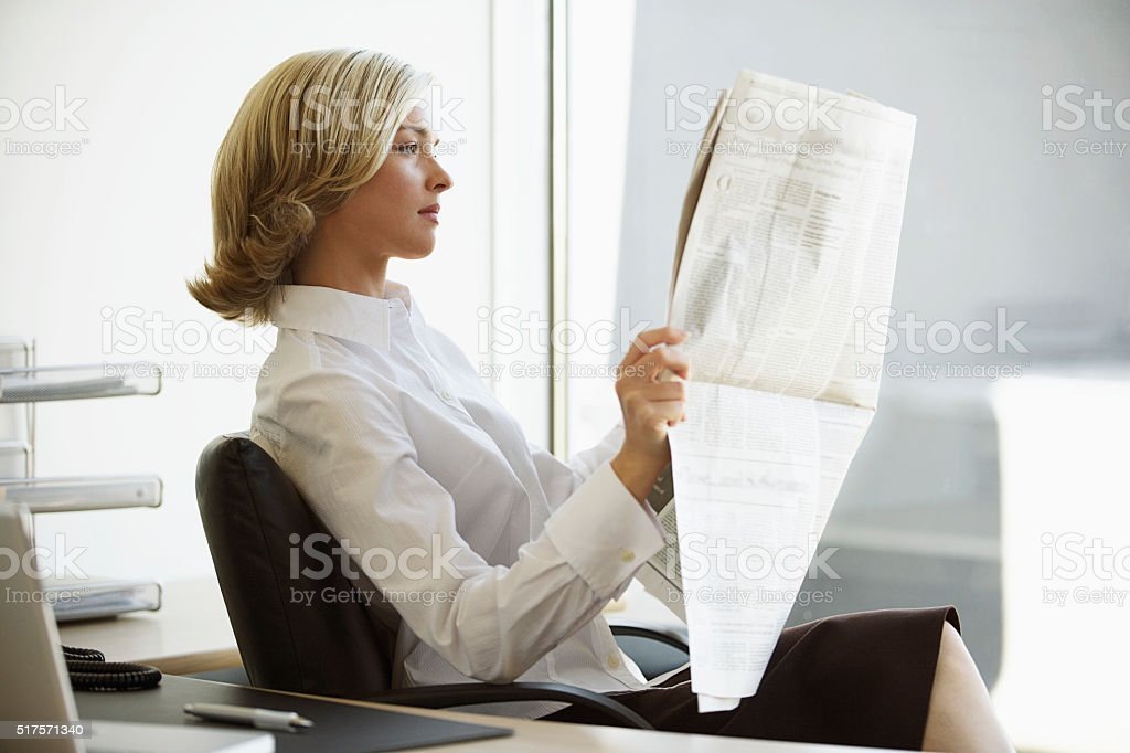 Businesswoman reading the paper stock photo