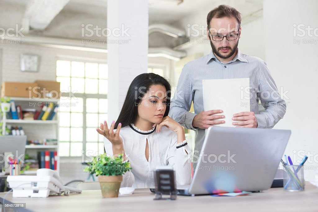 Businesswoman rebuking assistant at the office stock photo