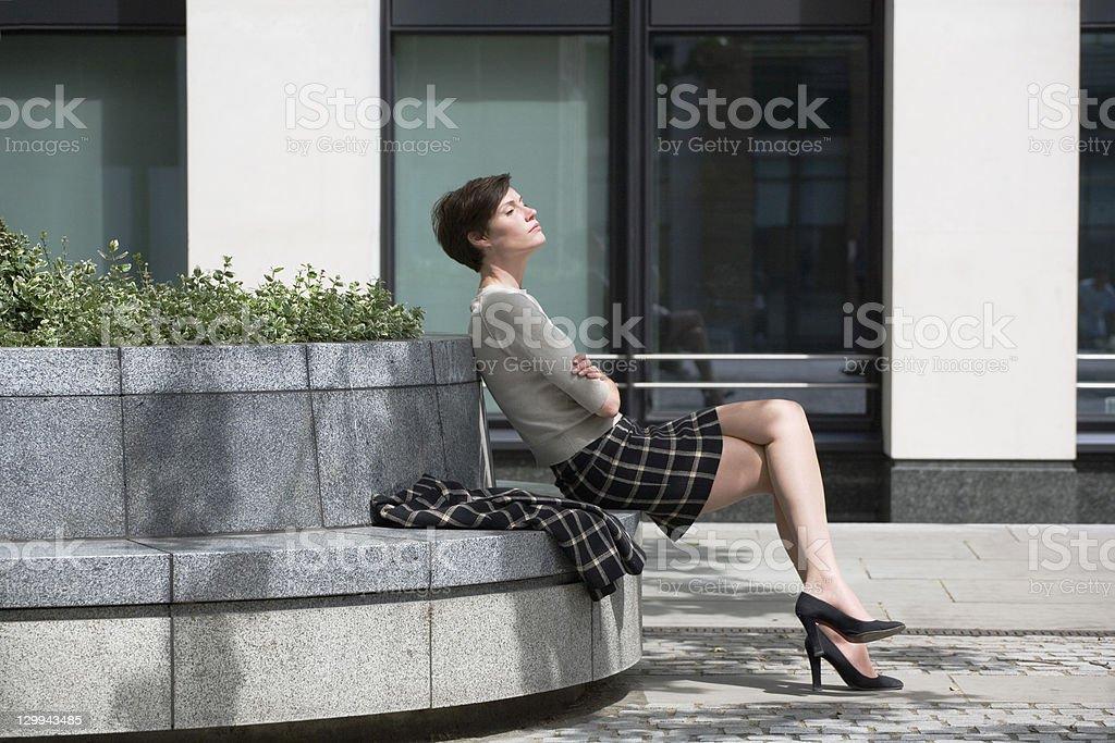Businesswoman relaxing in courtyard stock photo